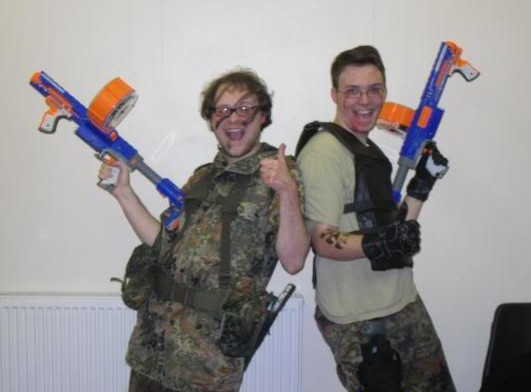 Two happy men with big NERF guns